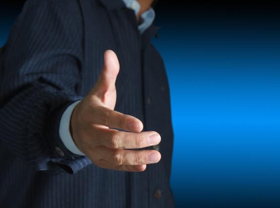 Businessman offering for handshake on dark blue background